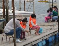 小さな子どもでも約30秒じっと待てれば、ハゼが釣れる。ボート釣りをする家族も見られた=千葉県市川市の江戸川放水路で