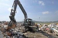 重機を使って災害ゴミを撤去する自衛隊員=岡山県倉敷市真備町地区で2018年7月13日午前9時15分、平川義之撮影