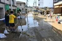 土砂の撤去が進められる冠水した道路=広島県府中町本町2で2018年7月13日午前9時26分、柴山雄太撮影