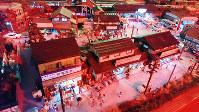 「夕景」タイムで明かりがともる駅前商店街の風景。生活する人々の姿が郷愁を誘う=兵庫県たつの市の昭和レトロ情景館で、桜井由紀治撮影