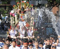 A Hakata Gion Yamakasa festival float is paraded through the central district of Fukuoka's Hakata Ward while water is thrown about on July 13, 2018. (Mainichi)