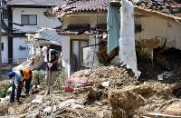 土砂に覆われた住宅を片付ける人たち=広島市安芸区矢野東で2018年7月13日午前11時1分、大西岳彦撮影