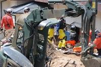 救助犬の反応があった場所周辺の土をかき出し、安否不明者を探す救助隊員ら=広島県坂町で2018年7月13日午前10時24分、三村政司撮影