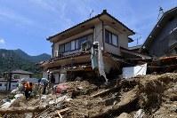土砂に覆われた住宅を片付ける人たち=広島市安芸区矢野東で2018年7月13日午前11時9分、大西岳彦撮影