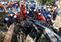 土砂崩れの現場で、手作業で土砂を撤去する消防隊員ら=広島県熊野町で2018年7月13日午前11時39分、小川昌宏撮影