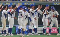 【王子(春日井市)-スバル(太田市)】十三回表王子1死二、三塁、矢幡の適時三塁打で生還した伊礼(手前左)と前田(同右)を迎える選手たち=東京ドームで2018年7月14日、山田尚弘撮影