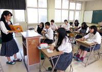ちょっと恥ずかしそうに、でも一生懸命絵本を読みます=大阪府立島本高校で、三角真理撮影