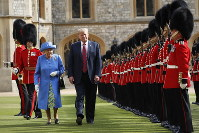 U.S. President Donald Trump with Queen Elizabeth II, inspects the Guard of Honour at Windsor Castle in Windsor, England, on July 13, 2018. (AP Photo/Pablo Martinez Monsivais)