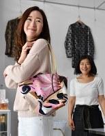 洋服をリメークして出来上がったかばんを受け取り笑顔の橘享子さん(左)=大阪市西区で、猪飼健史撮影