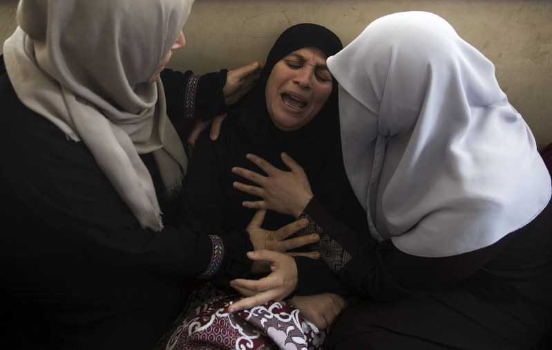 Relatives of 15-year-old Othman Hilles mourn during his funeral in the family home in Gaza City Saturday