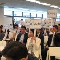 ママたちのスピーチを聞き、「いつか一緒に働きたい」と思った企業の経営者や採用担当者が「いいね!」の札を掲げる=東京都中央区で