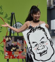 歌いながら即興で描いた似顔絵を披露する桜小路富士丸さん。絵は記念にその場でモデルとなった客に贈られる=東京都目黒区で5月26日