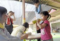 水につかった地域の幼稚園から園児を受け入れている市立薗幼稚園。熱中症対策としてクーラーボックスで冷やした水やお茶を30分ごとに園児に飲ませているという=岡山県倉敷市真備町地区で2018年7月15日、小松雄介撮影