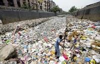 ごみで埋まった水路でプラスチックごみをより分けている男性。ごみはガンジス川を経由してインド洋へ流れる=ニューデリーのタイムール・ナガル地区で2018年6月12日、松井聡撮影