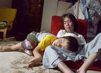子どもたちはお父さんが大好きだ。長男・敏暉(としき)さんは、遊んでいるうちに大谷喜久さんの膝の上で眠ってしまった=兵庫県宝塚市で、大谷さん提供