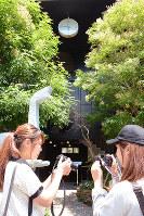 震災が発生した5時46分で止まったままの時計の写真を撮る大学生たち=神戸市中央区中山手通1で、黒川優撮影