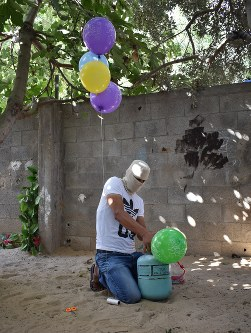 A masked man inflates balloons with car air conditioner coolant in the Gaza Strip on July 4, 2018. (Mainichi)