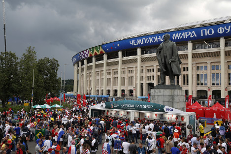 In this July 11, 2018 photo, sponsors' promotional booths surround a statue of Lenin as fans arrive for the semifinal match between Croatia and England at Luzhniki Stadium during the 2018 soccer World Cup in Moscow, Russia. AP Photo/Rebecca Blackwell)