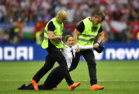 Stewards pull a woman off the pitch after she stormed onto the field and interrupted the final match between France and Croatia at the 2018 soccer World Cup in the Luzhniki Stadium in Moscow, Russia, on July 15, 2018. (AP Photo/Martin Meissner)