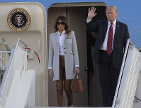 U.S. President Donald Trump, right, waves as he and his wife Melania arrive at the airport in Helsinki, Finland, on July 15, 2018 on the eve of his meeting with Russian President Vladimir Putin. (AP Photo/Markus Schreiber)