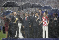 FIFA President Gianni Infantino, Russian President Vladimir Putin, French President Emmanuel Macron and Croatian President Kolinda Grabar-Kitarovic, from left, stand for the presentation in the rain after the final match between France and Croatia at the 2018 soccer World Cup in the Luzhniki Stadium in Moscow, Russia, on July 15, 2018. France won the final 4-2. (AP Photo/Matthias Schrader)