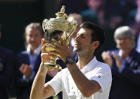 Serbia's Novak Djokovic lifts the trophy after winning the men's singles final match against Kevin Anderson of South Africa, at the Wimbledon Tennis Championships, in London, on July 15, 2018.(AP Photo/Kirsty Wigglesworth)