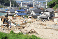 Damaged homes are seen in the Koyaura district of Saka, Hiroshima Prefecture, where the division between the Tenchi River and residential areas is no longer clear. (Mainichi)