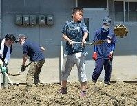 Naoki Morioka scoops up sediment with a shovel as a volunteer at a disaster hit area in the city of Kure, Hiroshima Prefecture, on July 15, 2018. (Mainichi)