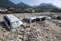 Cars remain buried in soil at a parking lot in Kure, Hiroshima Prefecture, on July 17, 2018. (Mainichi)