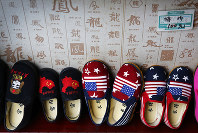 In this July 13, 2018 photo, Chinese made children shoes carrying a Chinese map and U.S. flags are on display for a sale at a shop in Beijing. (AP Photo/Andy Wong)