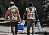 Construction workers carry large bottles of water during a break in the blistering days heat in downtown Los Angeles on July 6, 2018. (AP Photo/Richard Vogel)