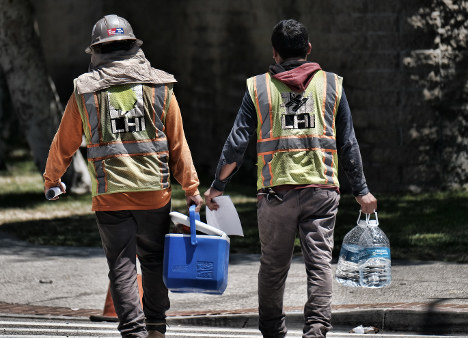 Construction workers carry large bottles of water during a break in the blistering day's heat in downtown Los Angeles on July 6, 2018. (AP Photo/Richard Vogel)
