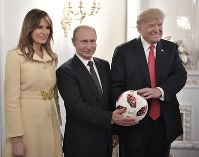 U.S. First Lady Melania Trump, left, Russian President Vladimir Putin, center, and U.S. President Donald Trump, pose with a soccer ball after a press conference following their meeting at the Presidential Palace in Helsinki, Finland, on July 16, 2018. (Alexei Nikolsky, Sputnik, Kremlin Pool Photo via AP)