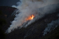Flames from the Ferguson Fire burn down a hillside in unincorporated Mariposa County California, near Yosemite National Park on July 15, 2018. (AP Photo/Noah Berger)