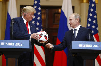 Russian President Vladimir Putin gives a soccer ball to U.S. President Donald Trump, left, during a press conference after their meeting at the Presidential Palace in Helsinki, Finland, on July 16, 2018. (AP Photo/Alexander Zemlianichenko)