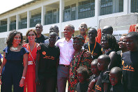 Former U.S. President Barack Obama, center, poses for a photo with his step Grandmother Sarah, center right, along with children and officials, during an event in Kogelo, Kisumu, Kenya, Monday, July 16, 2018. (AP Photo Brian Inganga)