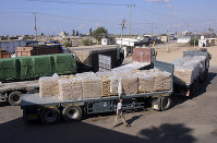 In this Oct. 14, 2014 photo, a Palestinian worker walks next to trucks loaded with sacks of cement at the Kerem Shalom border crossing on its way from Israel to Rafah in the southern Gaza Strip. (AP Photo/Eyad Baba)