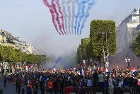 Smoke in the colors of the national flag is released by the French aerobatic squad on the Champs-Elysee avenue in Paris, on July 16, 2018. (Eric Feferberg/Pool Photo via AP)