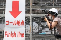 A member of the media takes a photo at the construction site of Sea Forest Waterway in Tokyo's Koto Ward on July 17, 2018, ahead of the 2020 Tokyo Olympics and Paralympics. (Mainichi)