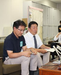 Naoki Suzuki, left, head of the school education division at the Toyoda Municipal Board of Education, and Takashi Yabushita, principal of the municipal Umetsubo Elementary School, meet reporters at the Toyoda Municipal Government office on July 17, 2018. (Mainichi)