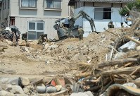 Self-Defense Force personnel continue a search for missing people near houses hit by a landslide in the city of Kure in Hiroshima Prefecture on July 17, 2018. (Mainichi)