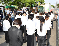 School officials and others offer silent prayers near the site where a June 18 earthquake toppled a wall along the grounds of a municipal elementary school and crushed nine-year-old Rina Miyake to death in the city of Takatsuki, Osaka Prefecture, on July 18, 2018. (Mainichi)
