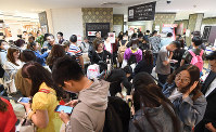 In this April 18, 2017 file photo, foreign tourists line up at a tax refund counter in the Takashimaya Osaka Store in Osaka's Chuo Ward. (Mainichi)
