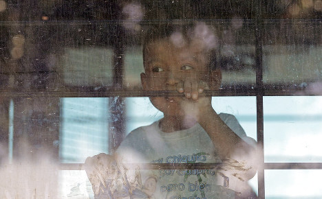 In this June 23, 2018 photo, an immigrant child looks out from a U.S. Border Patrol bus leaving as protesters block the street outside the U.S. Border Patrol Central Processing Center in McAllen, Texas. (AP Photo/David J. Phillip)