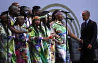 U.S. President Barack Obama, right, listens to members of the Soweto Gospel Choir sing the National Anthem at the 16th Annual Nelson Mandela Lecture at the Wanderers Stadium in Johannesburg, South Africa, on July 17, 2018. (AP Photo/Themba Hadebe)