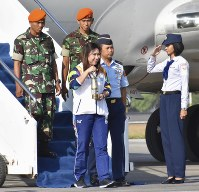 Indonesian badminton legend Susy Susanti (C) holds a container of the Asian Games flame in Yogyakarta, Indonesia, on July 17, 2018, after arriving from New Delhi, India. (Kyodo)