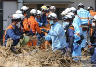 Rescue workers continue to search for missing people in the town of Saka, Hiroshima Prefecture, on July 19, 2018. (Mainichi)