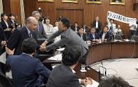 参院内閣委員会でカジノを含む統合型リゾート(IR)実施法案について予定時間を過ぎていた討論中に採決が始まり、抗議のため柘植芳文委員長(左)に詰め寄る自由・山本太郎氏(中央)と野党議員たち(左奥)=国会内で2018年7月19日午後4時40分、川田雅浩撮影