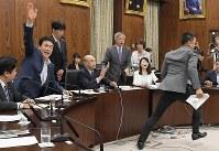 参院内閣委員会でカジノを含む統合型リゾート(IR)実施法案について予定時間を過ぎていた討論中に採決が始まり、柘植芳文委員長(中央)に阻止のため駆け寄った自由・山本太郎氏(右端)と抗議する野党議員たち(奥右)。左から2人目は賛成のため挙手を促す自民党議員=国会内で2018年7月19日午後4時40分、川田雅浩撮影