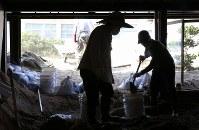 土砂が流れ込んだ家を掃除する菅廣順子さん(左)と夫の賢次さん。母の大畠祐子さん(96)を自宅で亡くした。祐子さんは着物の着付けを教えてくれたり、高齢でも自転車を乗り回すほど足腰の強い元気な人だったという=広島県坂町で2018年7月19日午前9時13分、宮武祐希撮影